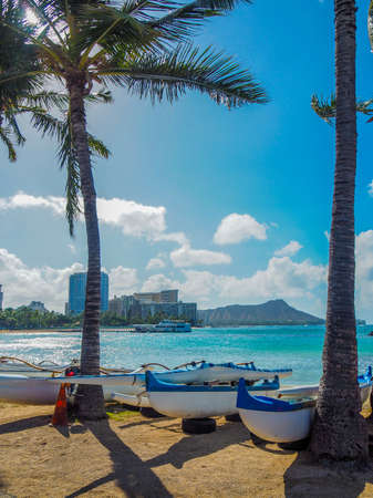 Canoes on a Hawaiian beach with Diamond Head Volcano in the background