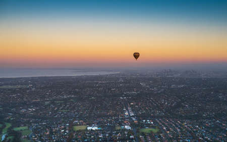 Australia, Melbourne - April 04, 2016: Hot Air Balloon above Melbourne city skyline with clear and calm sunrise