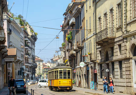 Italy, Milan - April 25, 2013: Historic Tram and traffic on the old paved Streets of Milan, Italy.