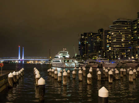 Australia, Melbourne - July 24, 2015: Melbourne Docklands at night with luxury yachts and Bolte Bridge