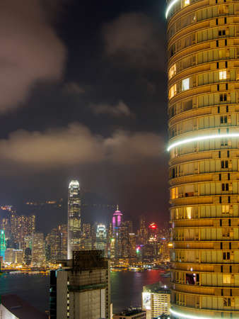 Hong Kong, Kowloon - November 11, 2014: Tall residential building in Kowloon with Hong Kong city skyline and skyscrapers in the background
