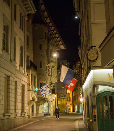Switzerland, Lucerne - March 24, 2015: A pedestrian walks along the old cobble stoned streets at night in the old town of Lucerne, Switzerland.