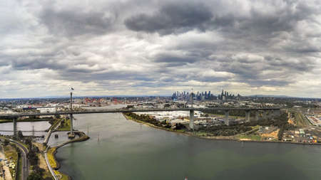 Australia, Melbourne - December 02, 2018: Aerial view of the West Gate Bridge and Melbourne city skyline with dark storm clouds 에디토리얼