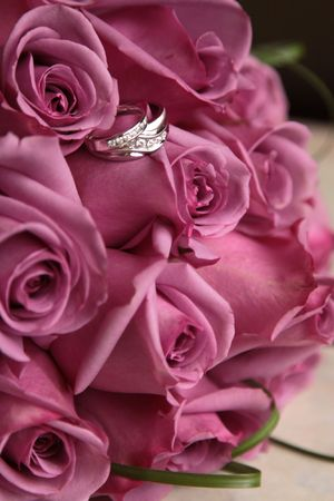 Wedding Rings in Bouquet of Pink Roses Stock Photo