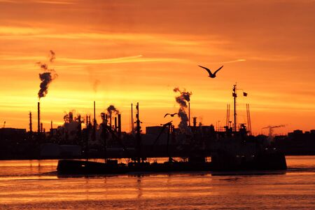 A silhouette of a refinery and boat with a bright orange sky, taken before sunrise photo