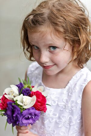 flowergirl: Cute flower girl holding a small bouquet of flowers Stock Photo