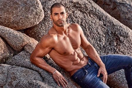 laying fitness man posing on the rocks