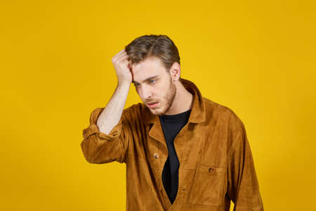 caucasian young man doing expressions on a yellow background