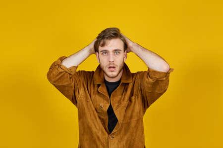 joven caucásico haciendo expresiones sobre un fondo amarillo Foto de archivo