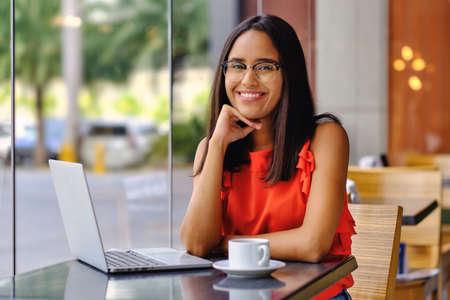 Latinamerican girl have a coffee break in a cafe Reklamní fotografie