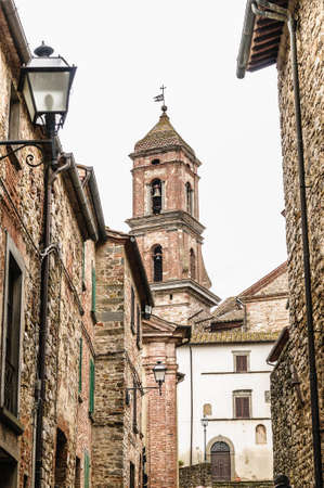 church steeple: Tradizionale vicolo villaggio italiano con muro in pietra, lampioni e un campanile di una chiesa