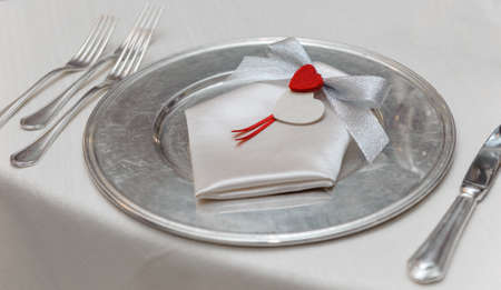 noble place setting with decoration bow with red heart, on bright tablecloth photo