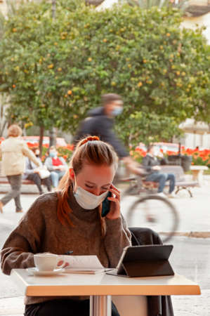 Young blonde girl with ponytail in her hair working or studying in a public cafe or restaurant with her tablet and mobile with a mask, vertical photography, in the background you can see the street and people passing in bicycle and walking