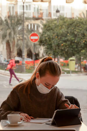 Young blonde girl with ponytail in her hair working or studying in a public cafe or restaurant with her tablet and mobile with a mask, vertical photography, in the background you can see the street and people passing by with a prohibition sign Stock fotó