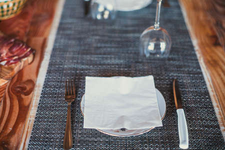 Light wooden table setting: white plates, rustic dark table cloth with salami, cheese, vine, and ham. Top view.