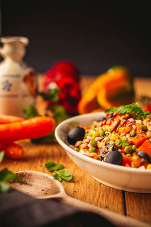 A view of a spelled dish on wooden background with some ingredients around: carrots, peppers, tomatos, parsley and oil