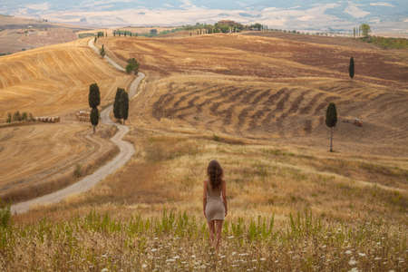 A girl in a countryside landscape in Val d'Orcia, Tuscany, Italy