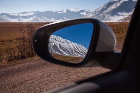 Mount Vettore seen from the mirror of the car, Piangrande, Castelluccio di Norcia, Italy Фото со стока