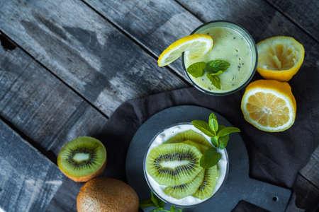 Homemade greek yogurt with kiwi, lemon and mint and healthy shack of kiwi, banana and lemon