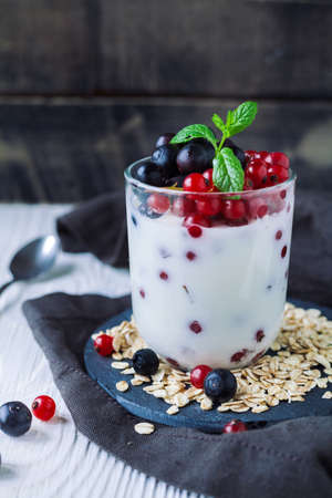Healthy homemade greek yogurt with ribes, blueberries, oatmeal and mint