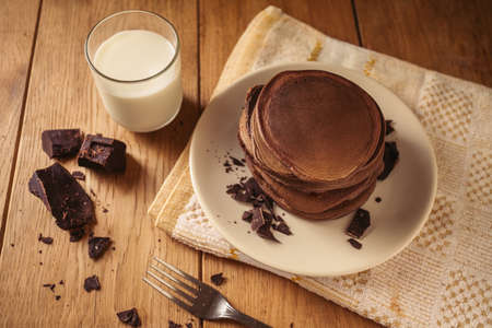 A view of delicious cocoa pancakes with dark chocolate and powdered sugar on a wooden table