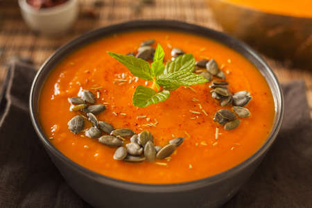 Pumpkin soup in the bowl with different ingredients.