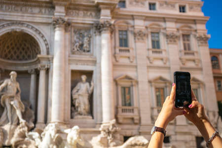 A girl is photographing the Trevi Fountain in Rome, Italy