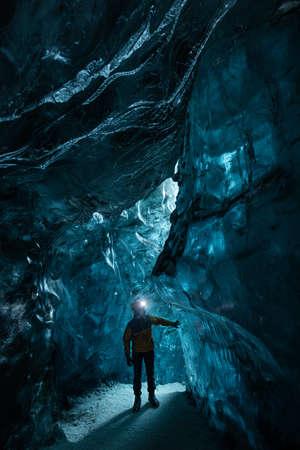 Explorer in the blue ice caves in Jökulsárlón glacier, Iceland, North Atlantic Ocean