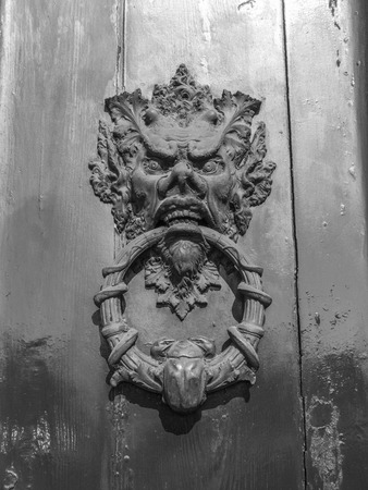 A devil on an old door Stock Photo