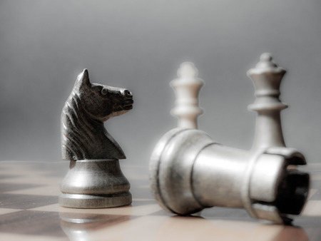 wooden chess pieces on a wooden chessboard in a dark background Stock Photo