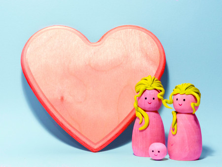 a gay wooden family on a soft background with an hart customizable for a wedding anniversary or st valentine day