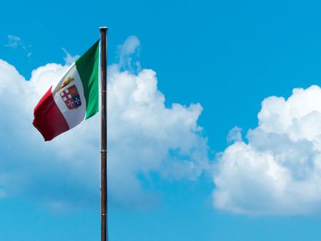 the italian navy flag waving on a blue cloudy sky background
