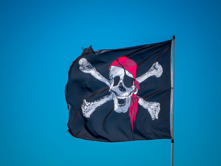 the pirates flag, the jolly roger, waving on a blue sky background
