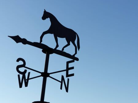 weathervane: an horse weathervane on a blue sky background