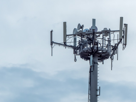 a telephone antenna with a cloudy sky background
