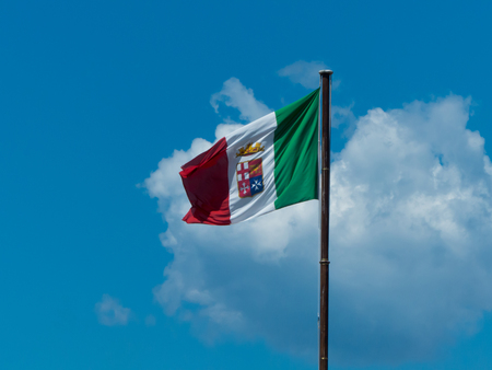 the italian navy flag waving on a blue cloudy sky background
