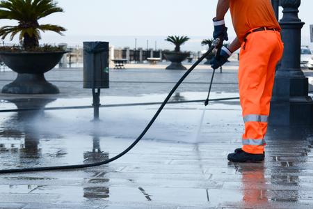 Un lavoratore con un'idropulitrice che pulisce la strada Archivio Fotografico - 85109773