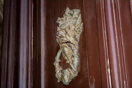 door handle: an ancient clapper on an ancient wooden door Stock Photo