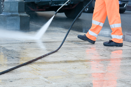 a worker with a pressure washer cleaning the street