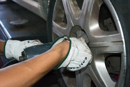 impact wrench: tyre repairer fixing a wheel using an impact wrench at the tyre shop Stock Photo