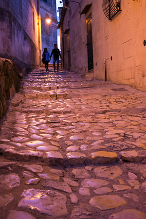 rupestrian: stone stair lightened by a street lamp in a alley of the city of matera at night