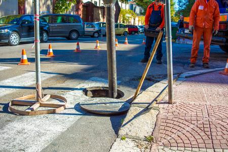 Een man beveelt een machine om de mangaten in de straat te reinigen Stockfoto