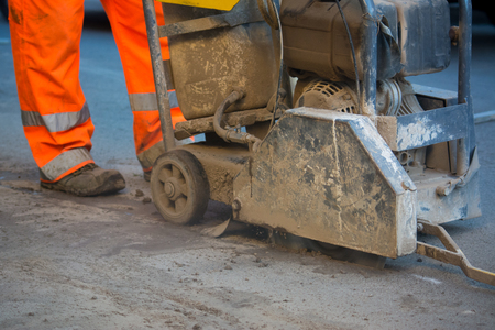 Close Up Of A Worker Dressing An Orange Uniform Driving A Machine To Cut The Asphalt In The Street