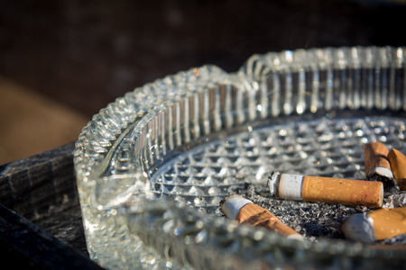 Close Up of A Glass Ashtray With Some Consumed Cigarettes On Blur Dark Background