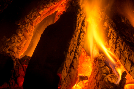 Close Up Of Burning Wood Pieces In a Fireplace On Dark Bacground