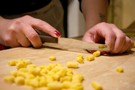 Hands Cutting The Knead Little Pieces With A Knife Preparing An Italian Traditional Food Called Strufoli On A Wooden Table Background. This Food Is Usually Prepared In Italy For Christmas And Carnival Holidays