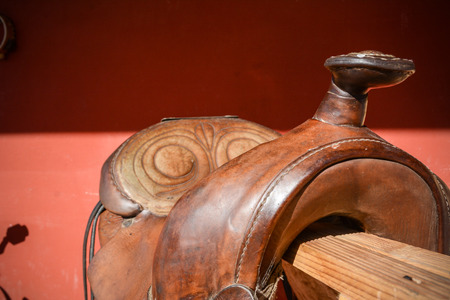 Horizontal View Of Close Up Of An Old Used Brown American Saddle On Red Blur Background