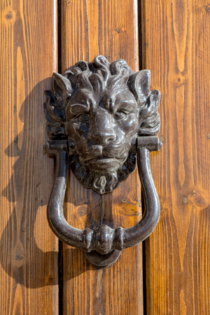 Horizontal View of Close Up of Old Clapper With The Shape of a LIon On a Wooden Door
