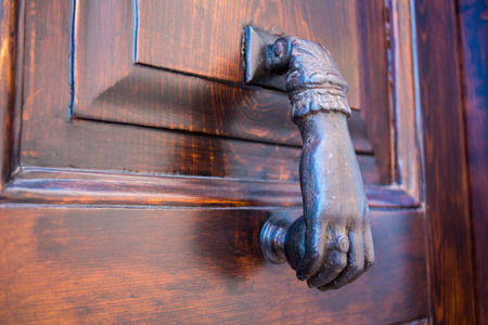 Horizontal View of Close Up of a Bronze Clapper With The Shape of an Hand On a Wooden Door