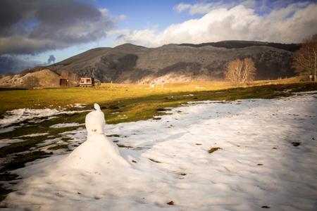 Vista horizontal de un muñeco de nieve que se está derritiendo durante un día caluroso en primavera en el fondo del paisaje de montaña de Blur